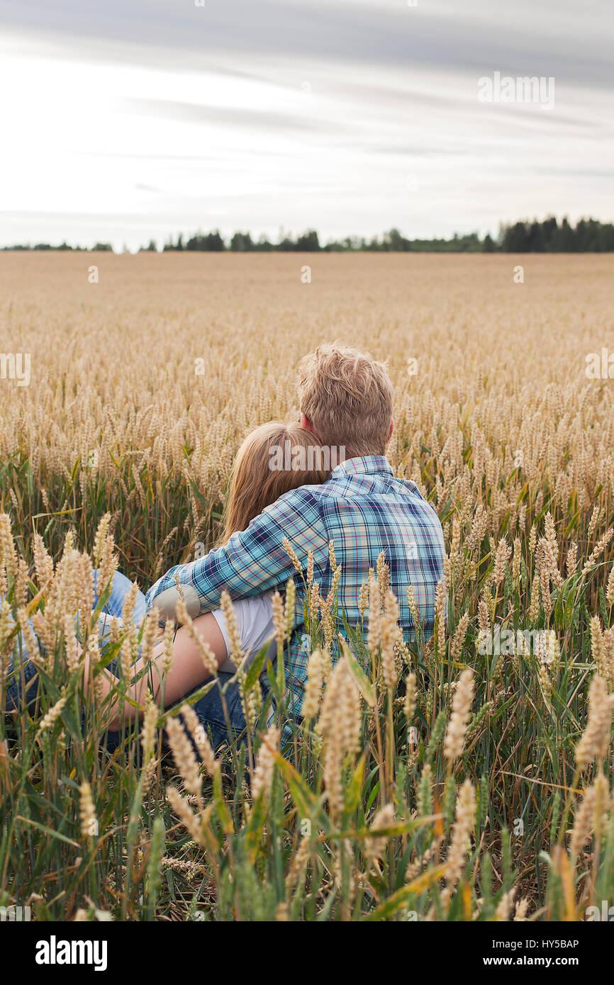 Finland, Uusimaa, Siuntio, Mid adult couple sitting in wheat field - Stock Image