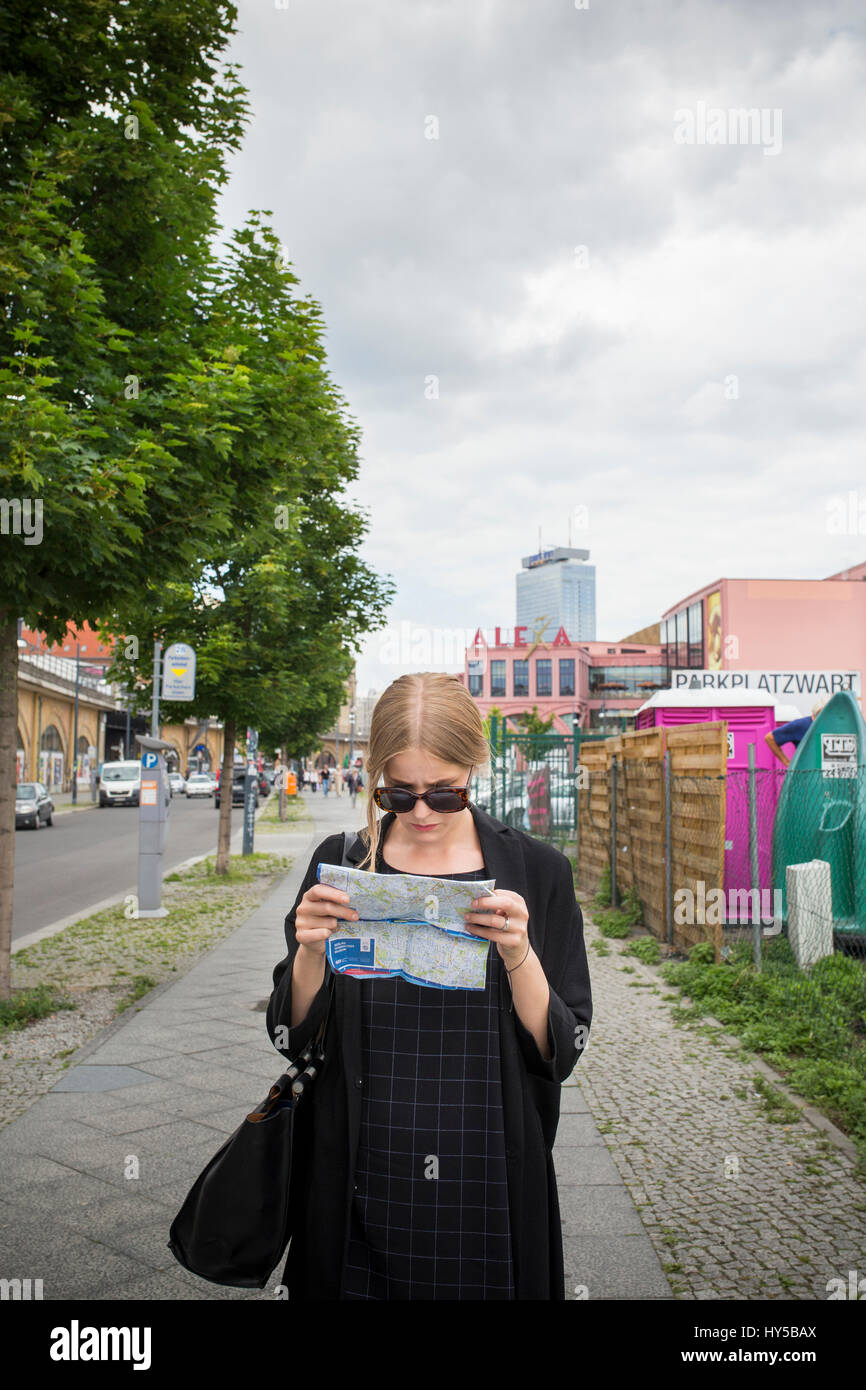 Germany, Berlin, Young woman with city map Stock Photo