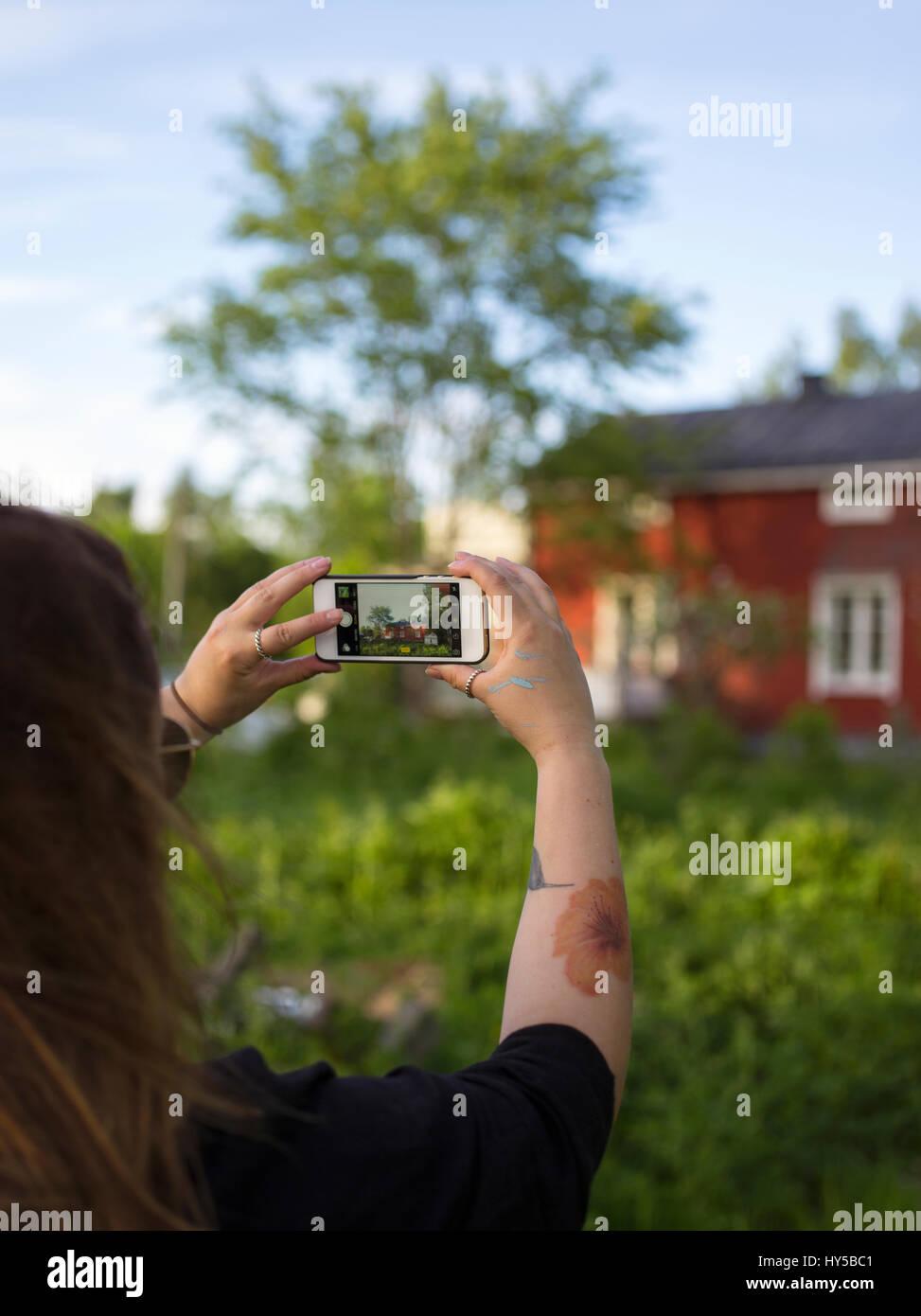 Finland, Ostrobothnia, Woman photographing house Stock Photo