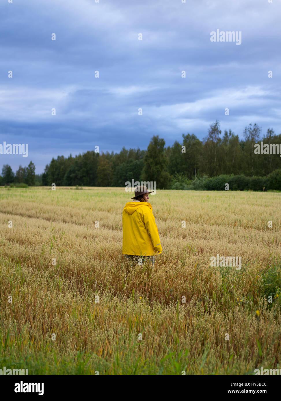Finland, Ostrobothnia, Kruunupyy, Woman wearing raincoat standing in field - Stock Image