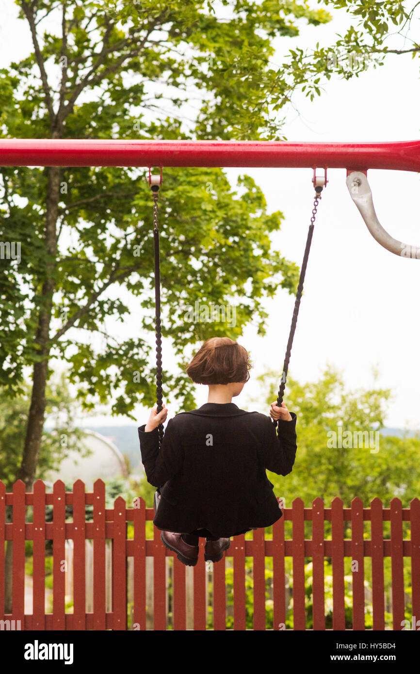 Finland, Pirkanmaa, Tampere, Young woman swinging in back yard - Stock Image