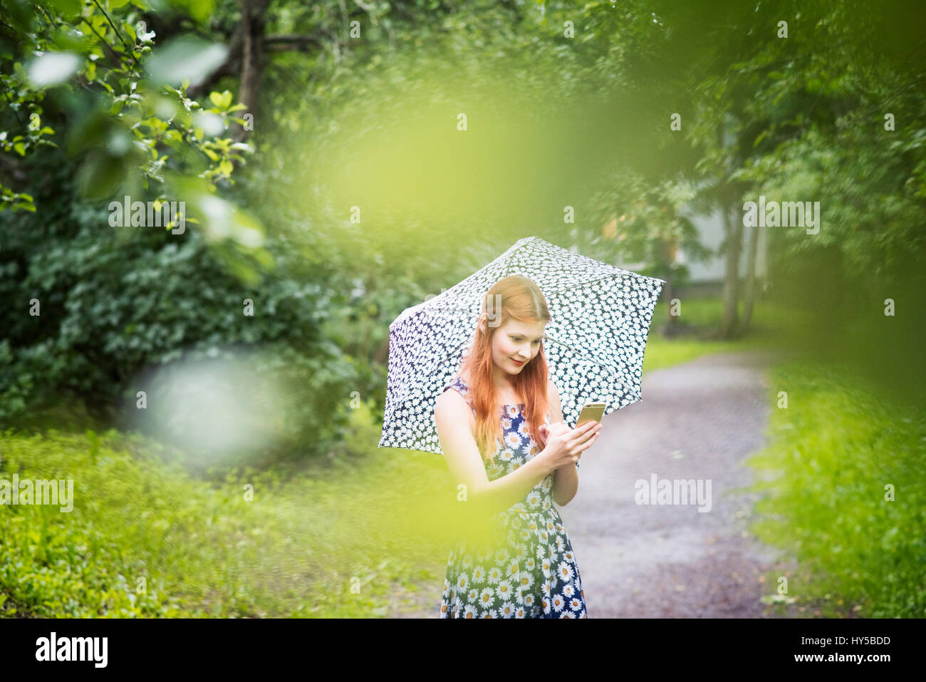 Finland, Pirkanmaa, Tampere, Woman wearing floral dress standing with umbrella in park - Stock Image