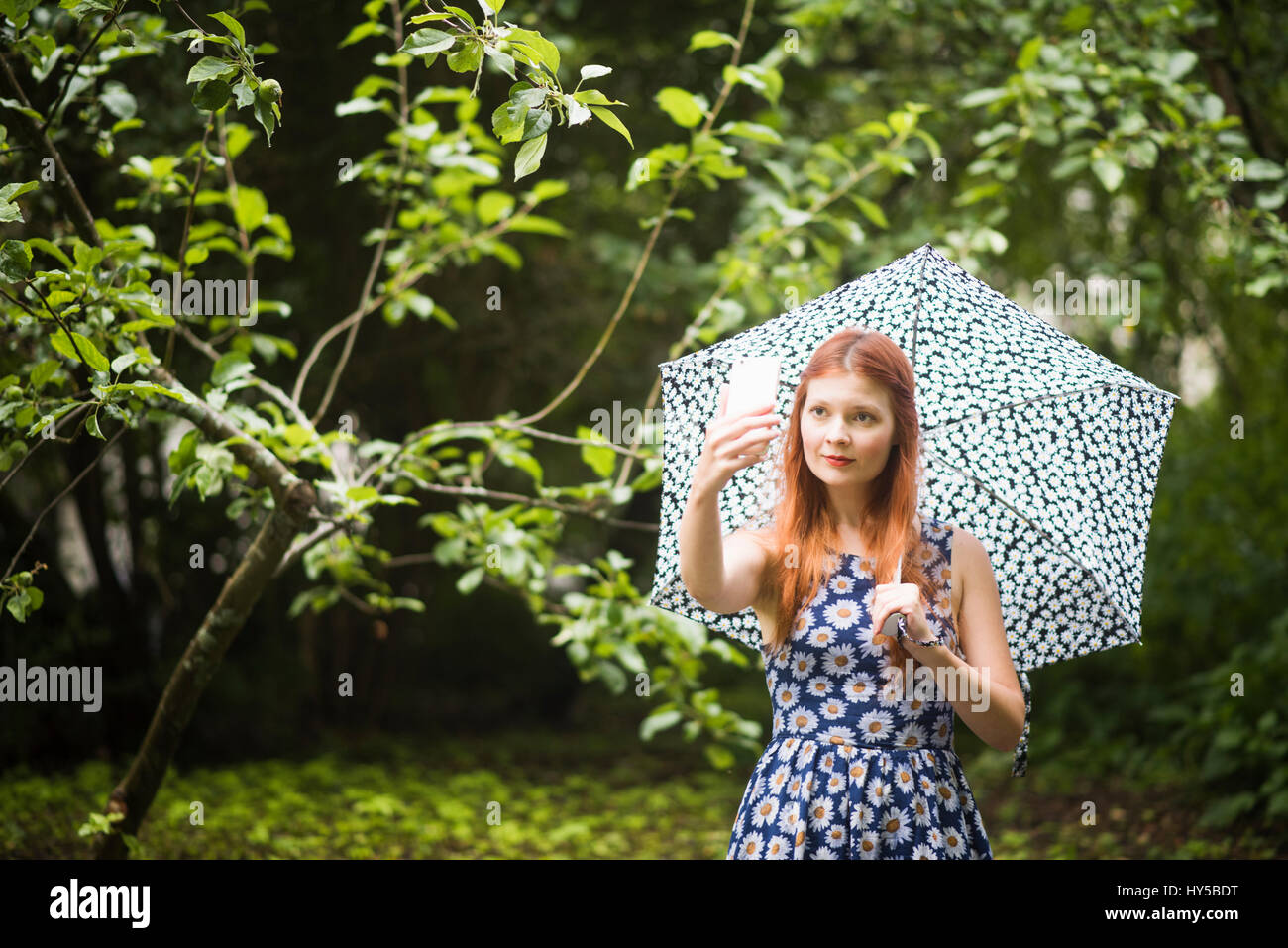 Finland, Pirkanmaa, Tampere, Woman wearing floral dress standing with umbrella in park and taking selfie Stock Photo