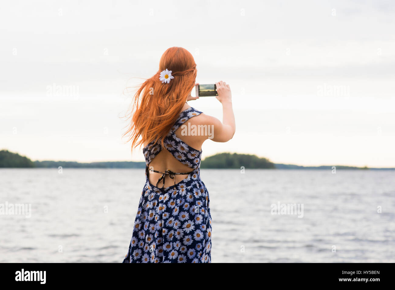Finland, Pirkanmaa, Tampere, Woman photographing sea - Stock Image