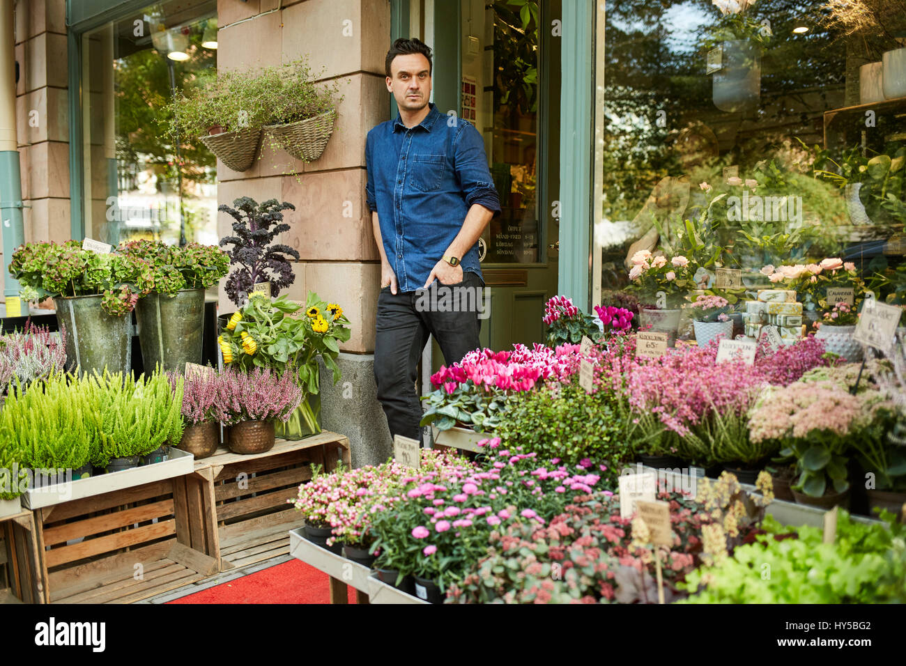 Sweden, Florist standing in front of entrance of flower shop - Stock Image