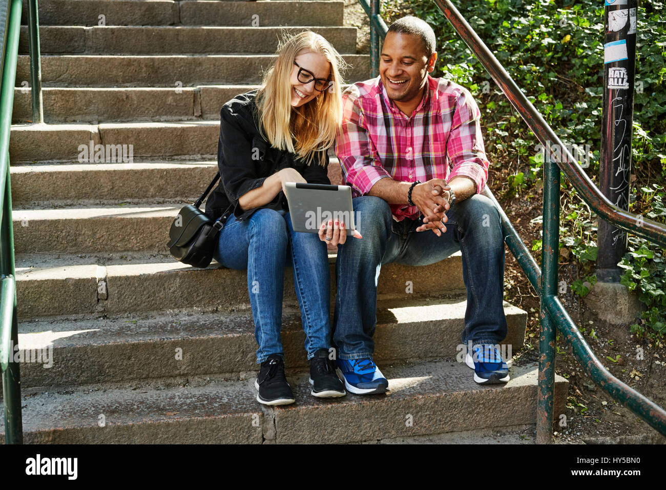 Sweden, Man and woman sitting side by side on steps and looking at digital tablet - Stock Image
