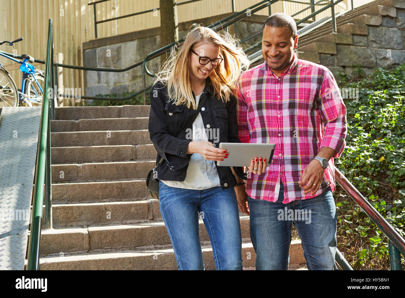 Sweden, Man and woman standing side by side in front of steps and looking at digital tablet - Stock Image