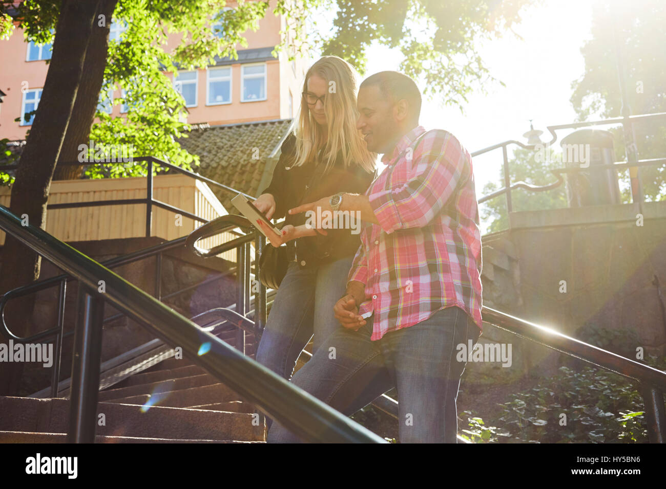 Sweden, Man and woman standing side by side looking at digital tablet in sunlight - Stock Image