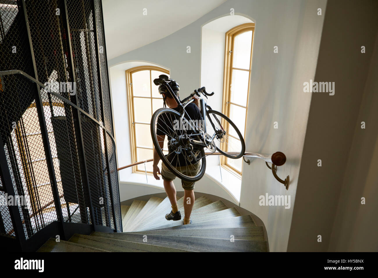 Sweden, Cyclist carrying bicycle on steps - Stock Image