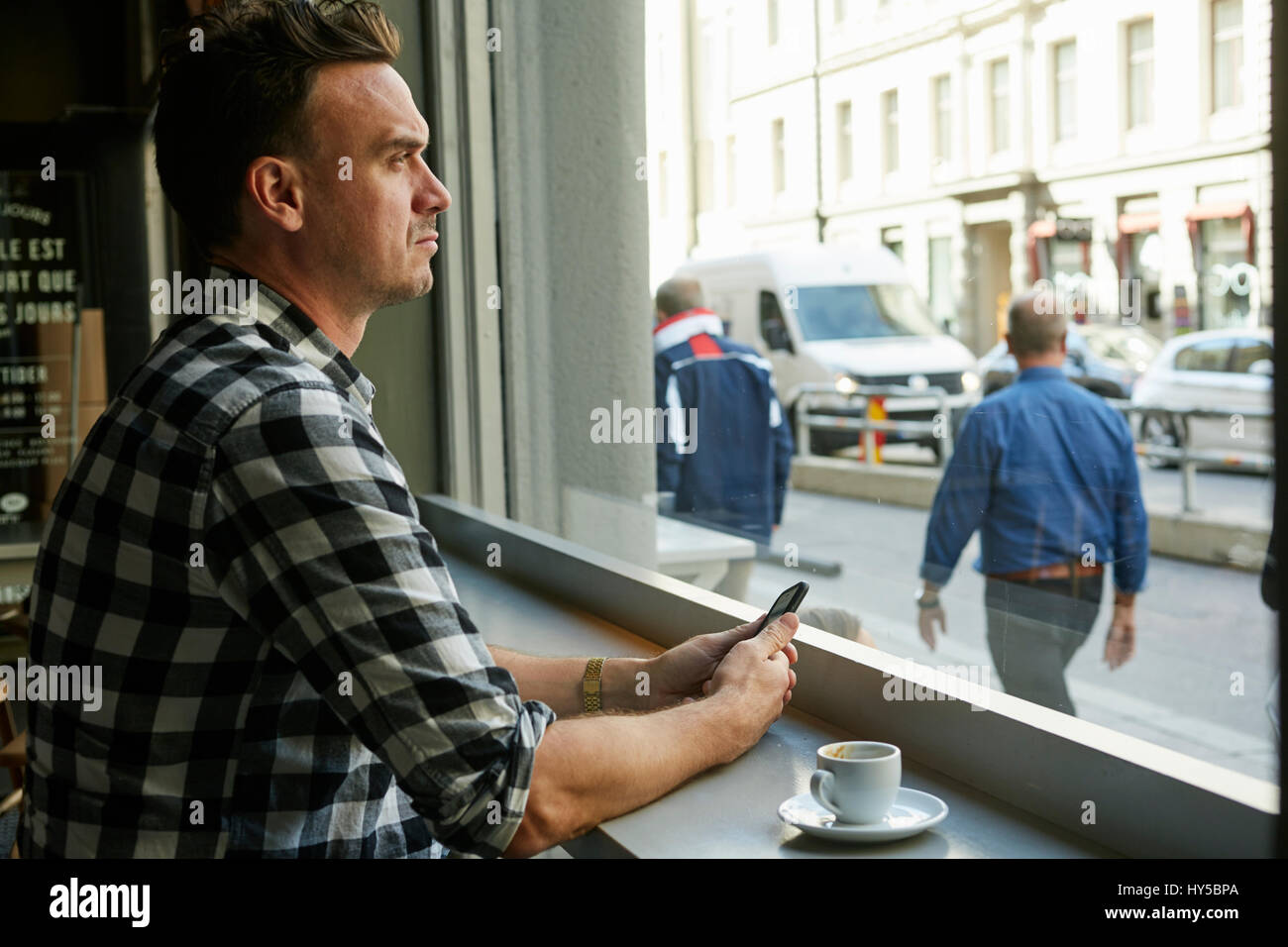 Sweden, Man holding cellphone and looking through window in cafe - Stock Image