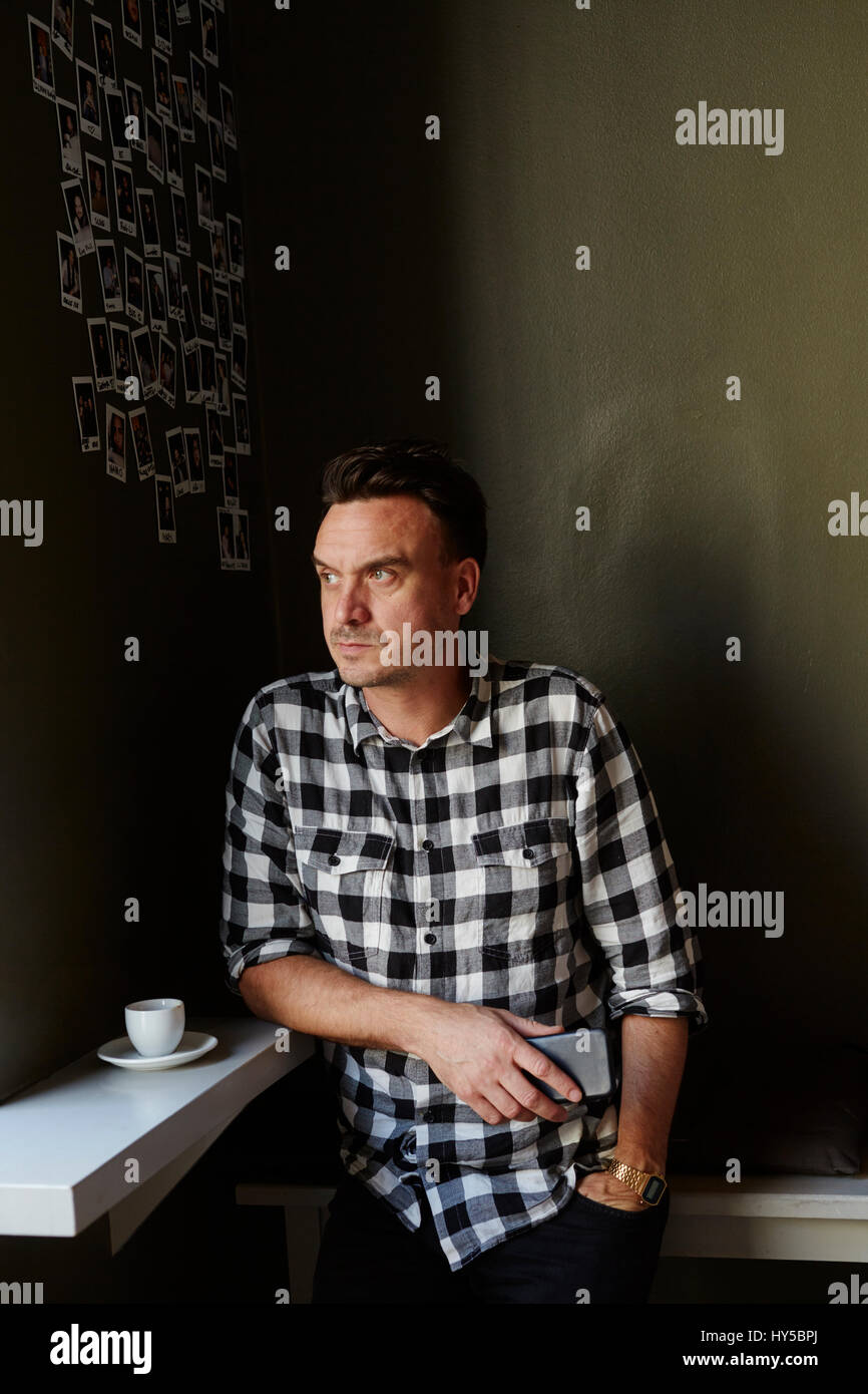 Sweden, Pensive man in cafe looking away and holding mobile phone - Stock Image