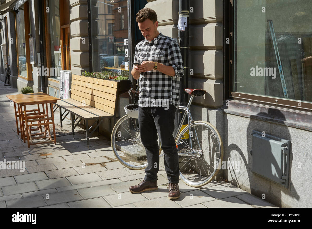 Sweden, Stockholm, Man texting on sidewalk - Stock Image