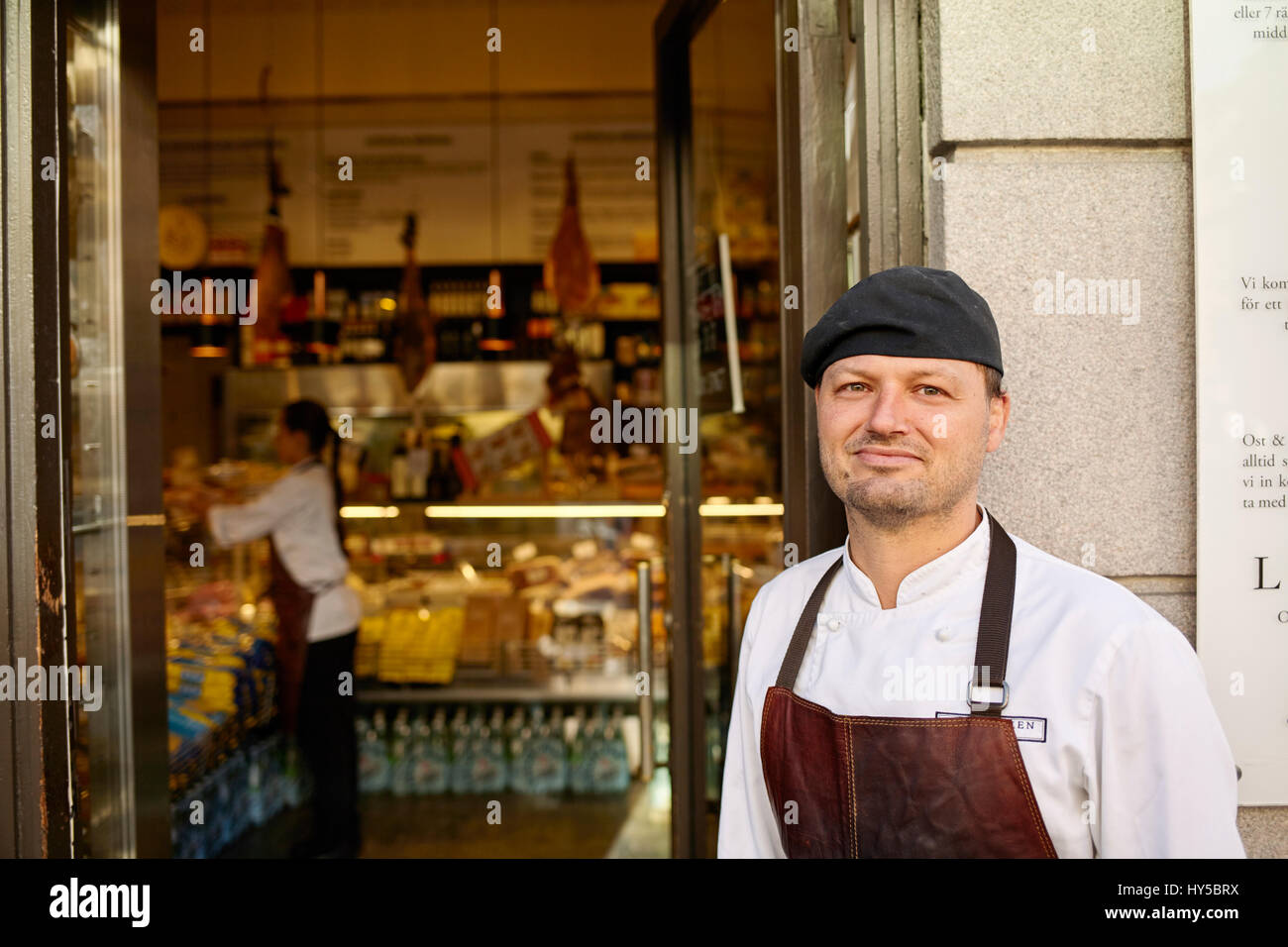 Sweden, Man in apron standing in front of store - Stock Image