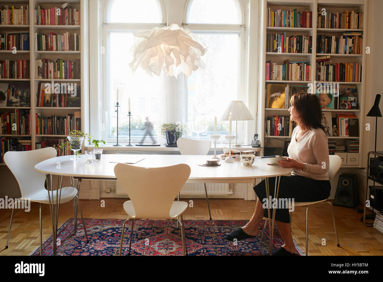 Sweden, Woman sitting alone at table - Stock Image