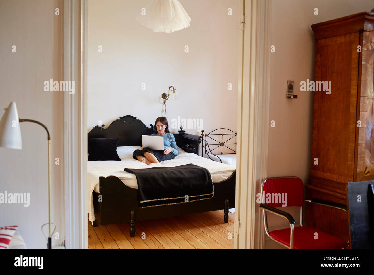 Sweden, Woman using laptop while sitting on bed - Stock Image