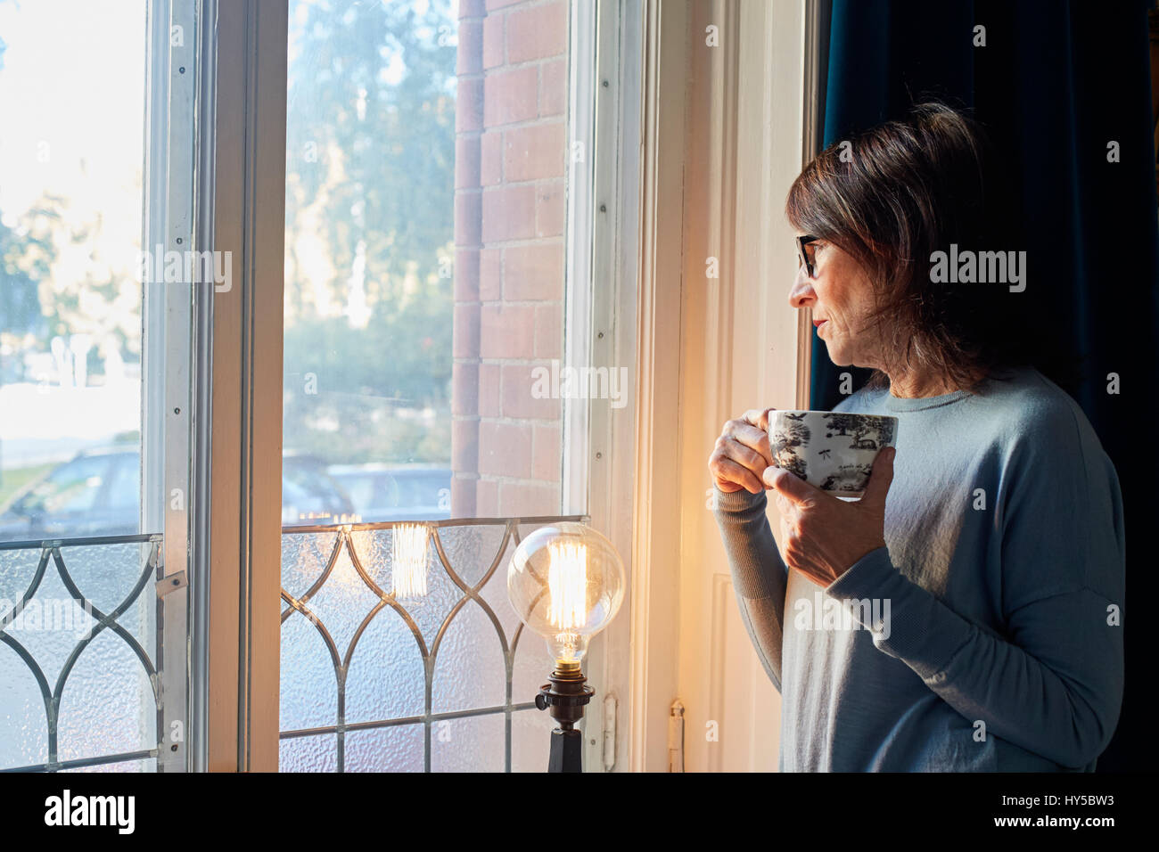 Sweden, Woman looking through window, holding coffee cup - Stock Image