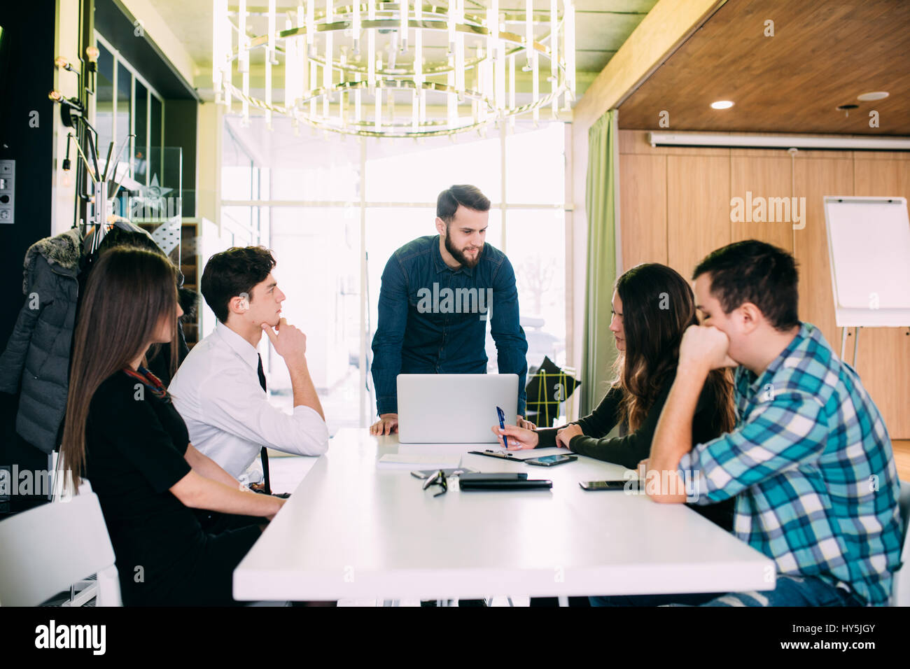 Young freelance team meeting at table discuss goals in modern office. Teamwork - Stock Image