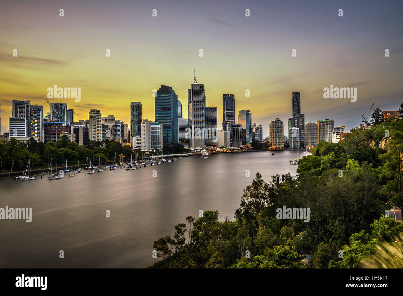 Sunset skyline of Brisbane city and Brisbane river  from Kangaroo Point Cliffs, Queensland, Australia. Long exposure. - Stock Image