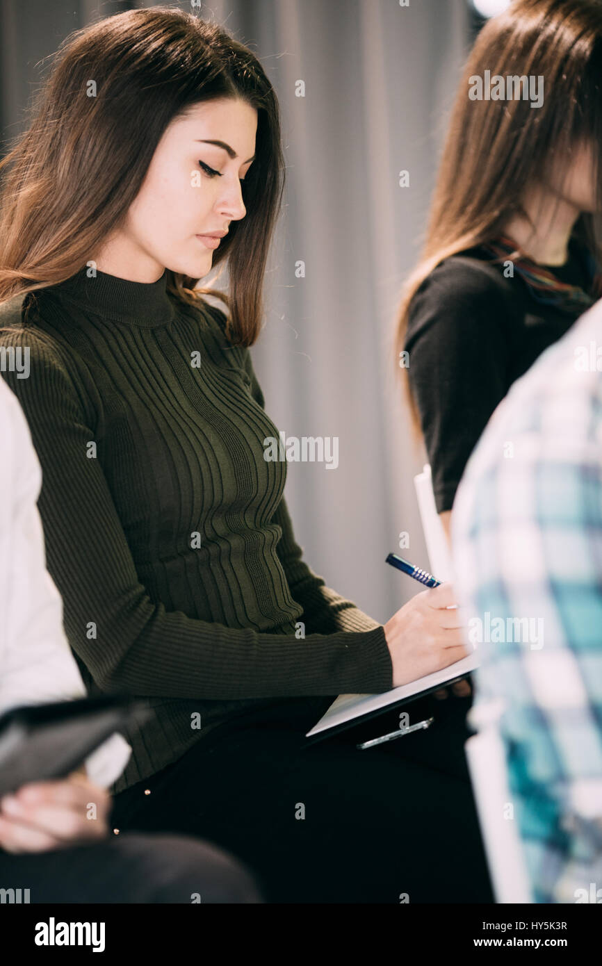 Close up of woman make notice at presentation on meeting of office teambuilding. Teamwork - Stock Image
