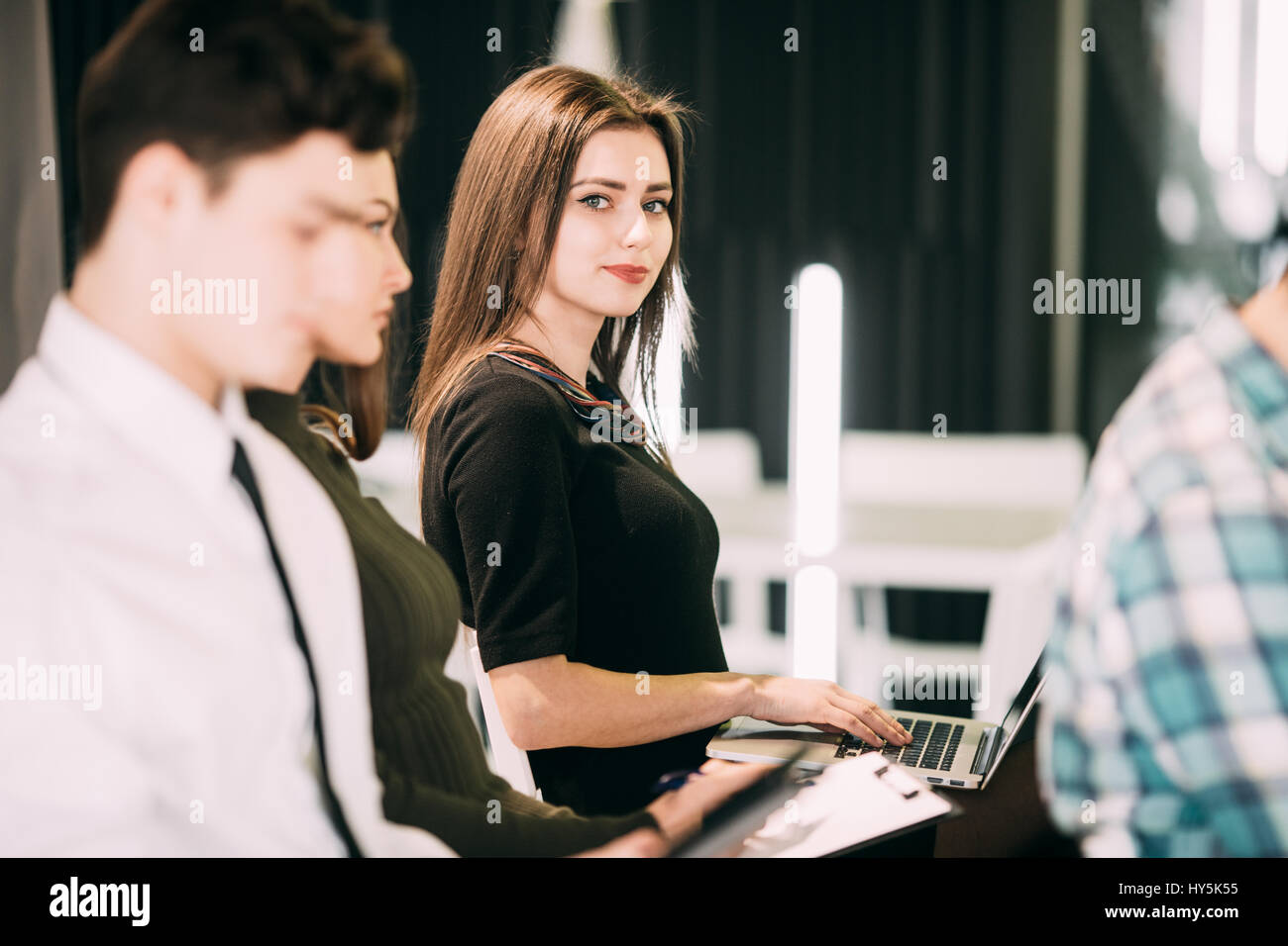 Close up of woman make notice in laptop at presentation on meeting of office teambuilding. Teamwork - Stock Image