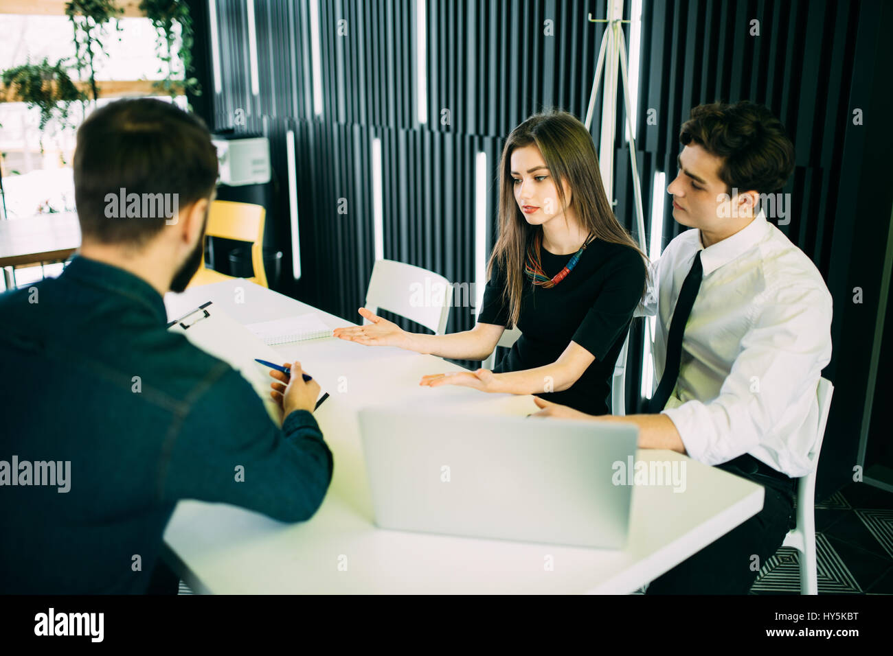 Broker making a presentation to couple showing them a document which they are viewing with serious expressions - Stock Image