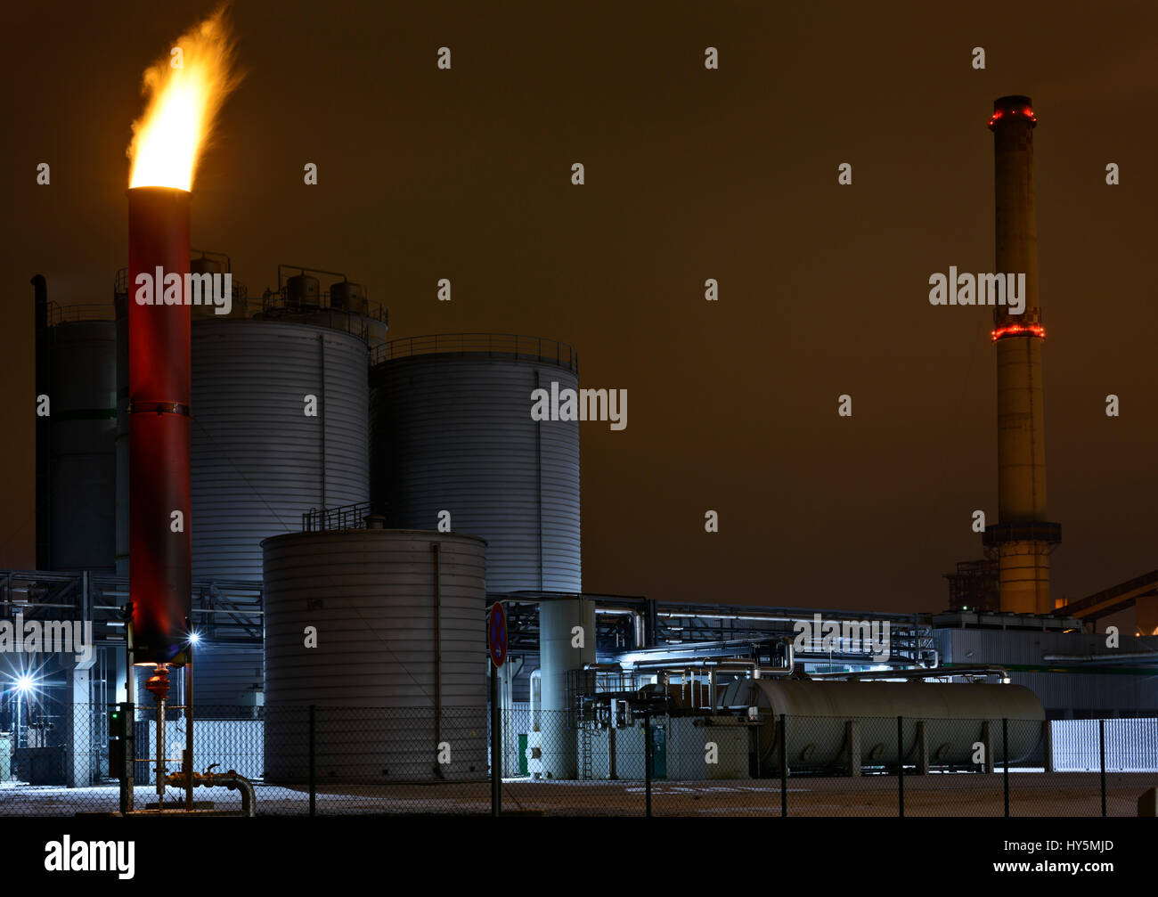 Sewage treatment plant at night. Clarifying gases are flared off. - Stock Image