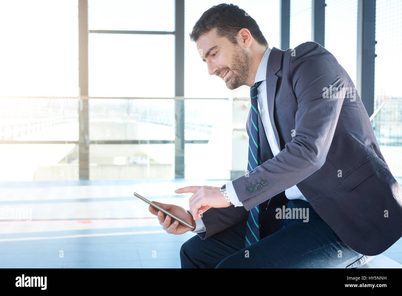Businessman is looking at his digital tablet while is going to work - Stock Image