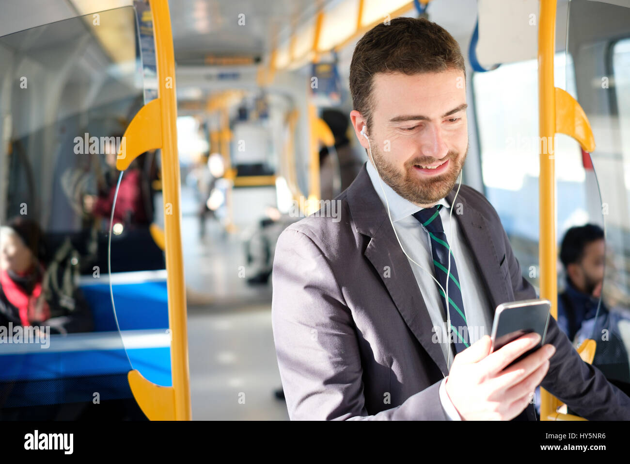 Businessman is looking at his mobile phone while is going to work Stock Photo