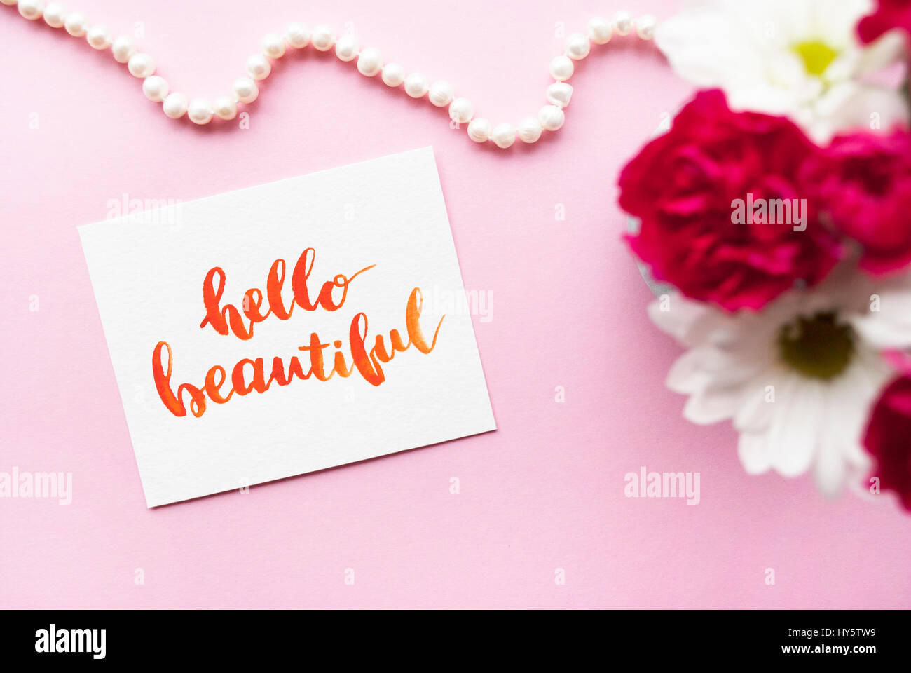 Inspirational quote Hello beautiful written in calligraphy style with watercolor. Composition on a pink background. - Stock Image