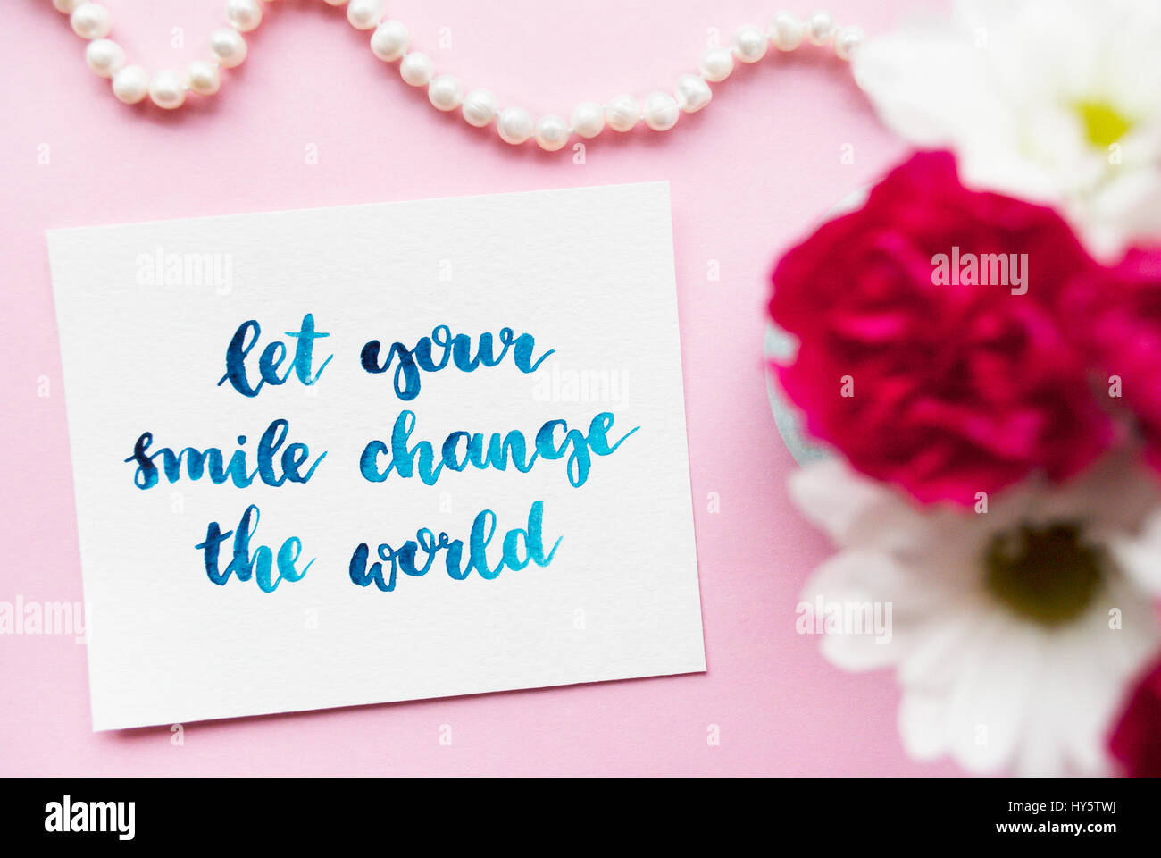 Inspirational quote Let your smile change the world written in calligraphy style with watercolor. Composition on - Stock Image