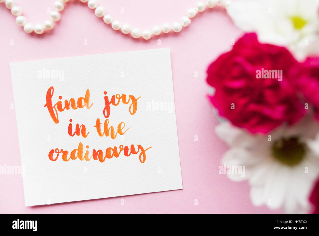 Inspirational quote Find joy in the ordinary written in calligraphy style with watercolor. Composition on a pink - Stock Image