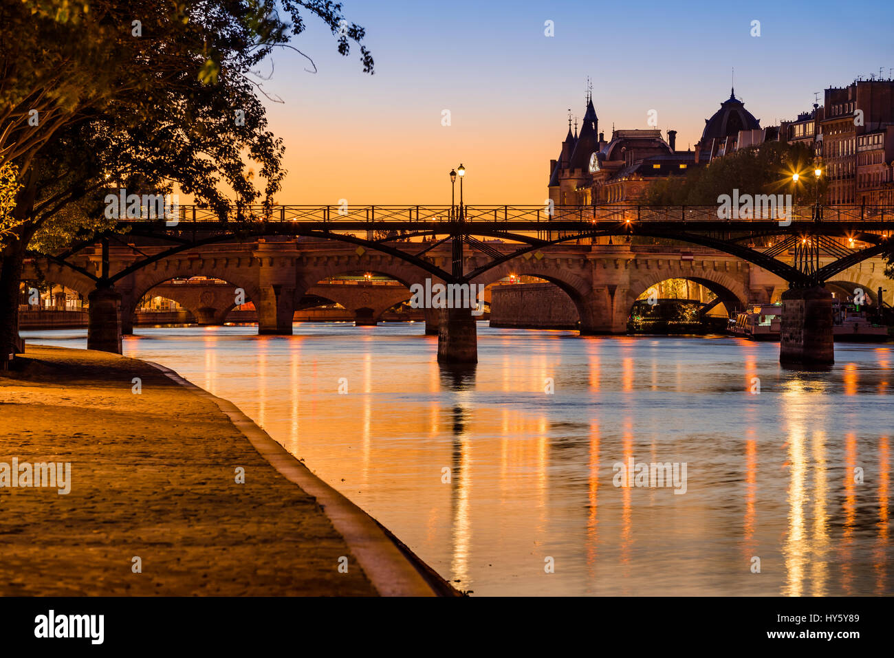 Sunrise on the Seine River banks, Pont des Arts and Pont Neuf in the 1st Arrondissement of Ile de la Cite, Paris, - Stock Image