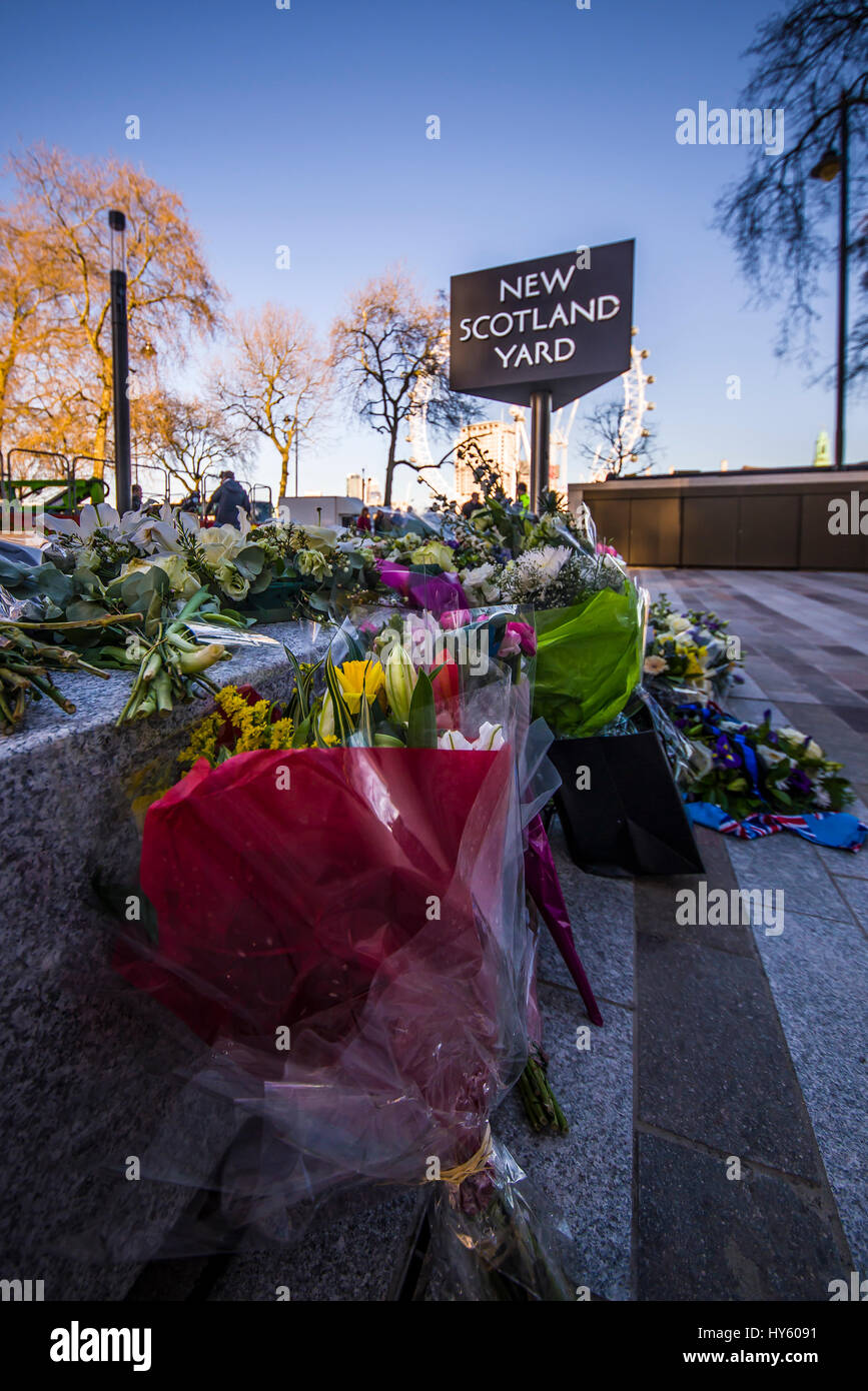 Floral tributes outside New Scotland Yard, London, following the terrorist action and death of PC Keith Palmer. - Stock Image