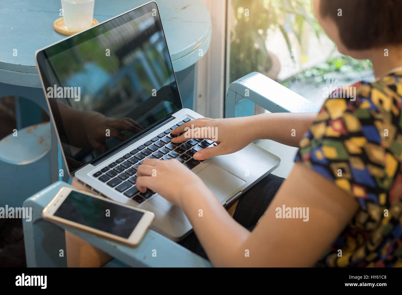 Young Asian woman working online at home with laptop computer. Freelance and outsource worker activity concept. - Stock Image