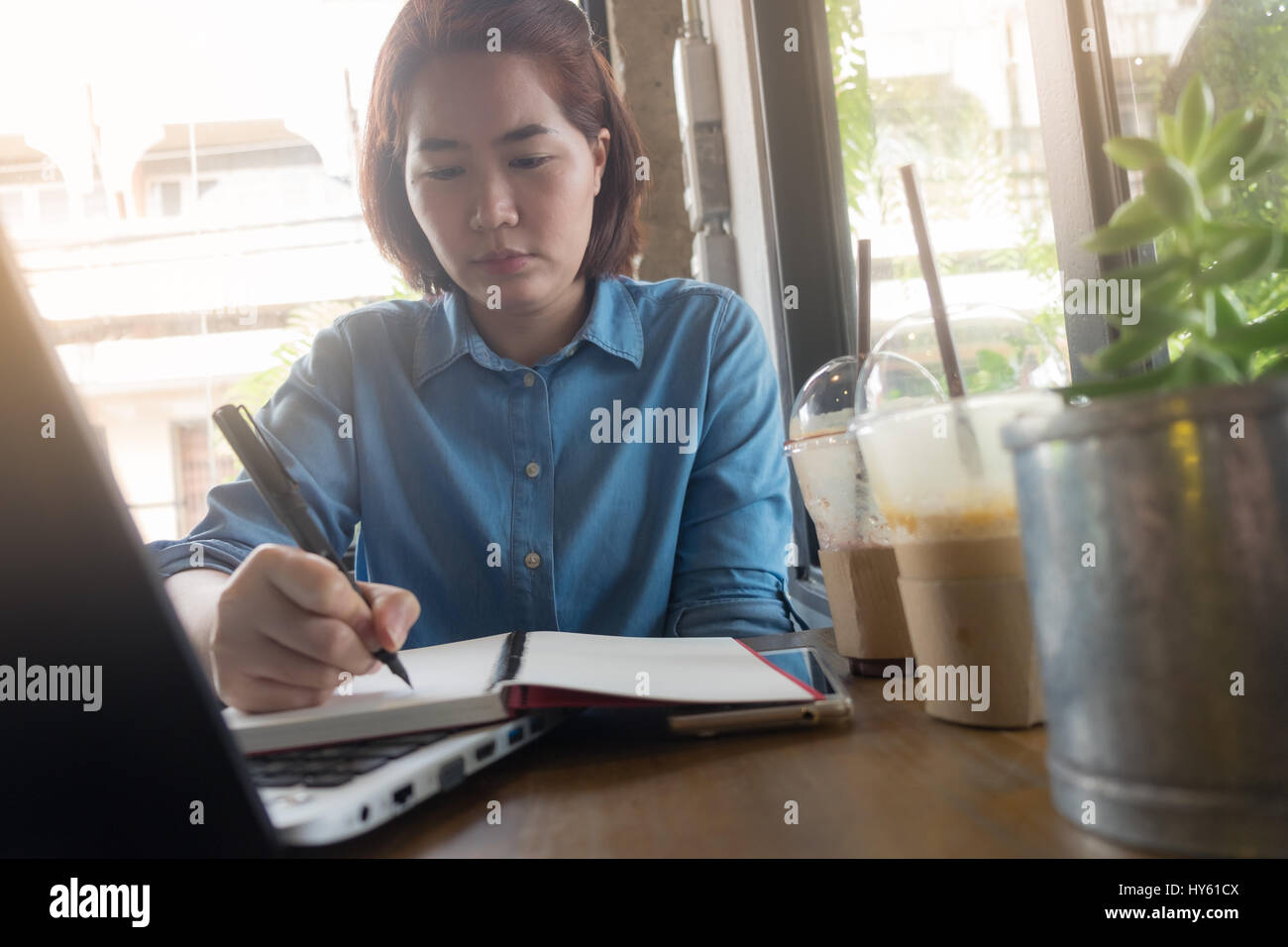 Young Asian hipster woman writing journal on notebook with serious emotion in coffee shop. Freelance business starup - Stock Image