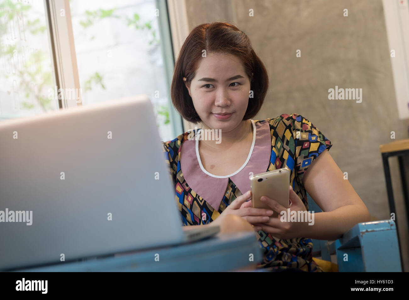 Asian woman using smartphone at home while working with laptop computer. Online business and wireless working from - Stock Image