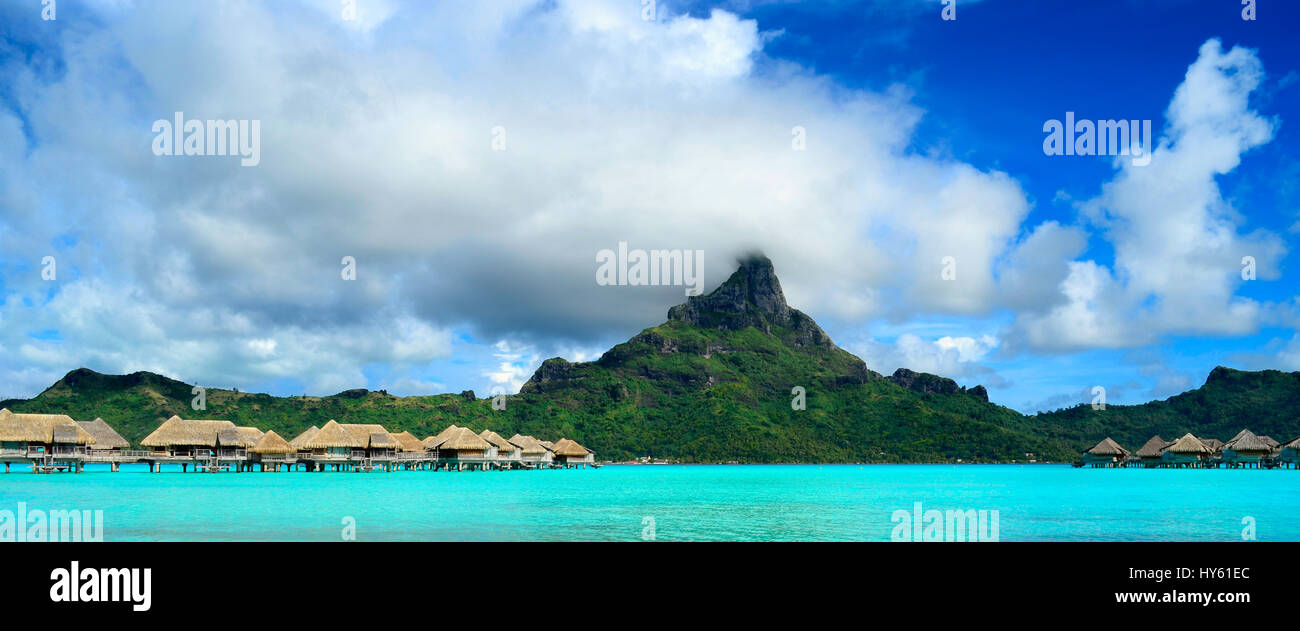 Panorama image of a tropical Bora Bora landscape with green Otemanu mountain behind a luxury resort in the turquoise - Stock Image