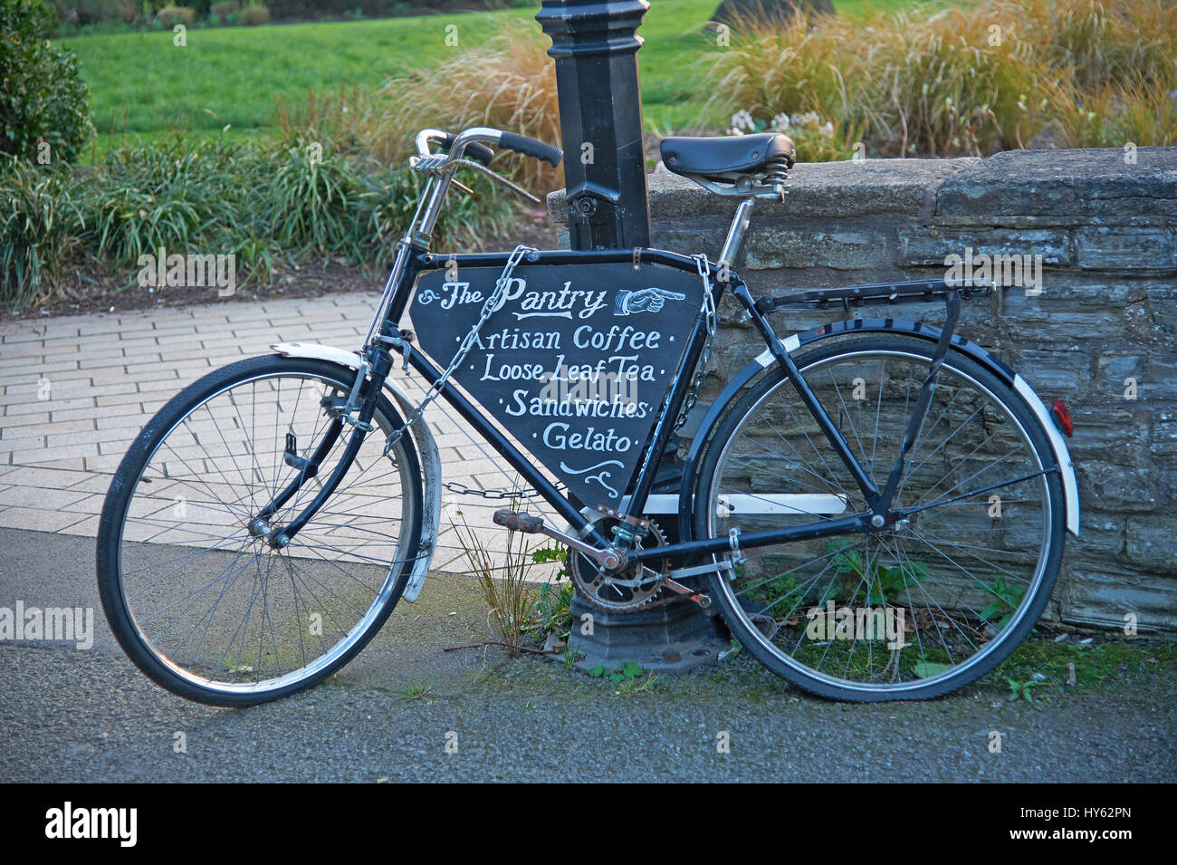 An old black bicycle chained to a lamp post and leaning against a stone wall. Stock Photo
