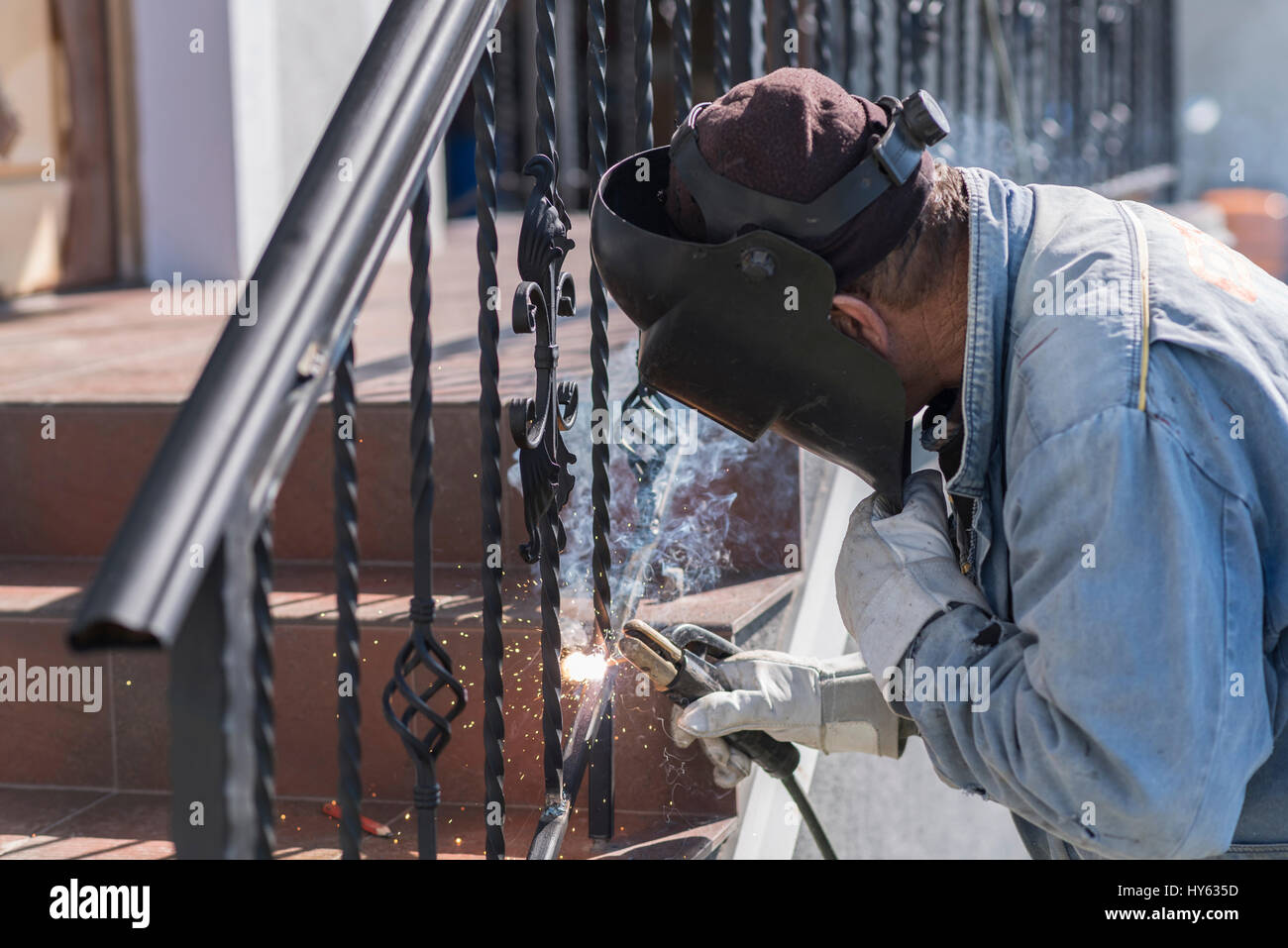 A Worker Welding Metal Handrails On The Stairs Wrought