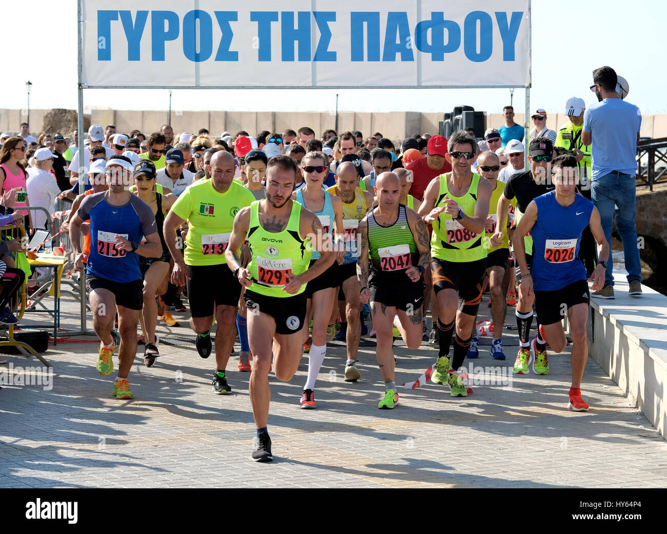 Athletes leave the start of the 10k road race in front of Paphos Castle, Paphos Harbour, Cyprus. - Stock Image
