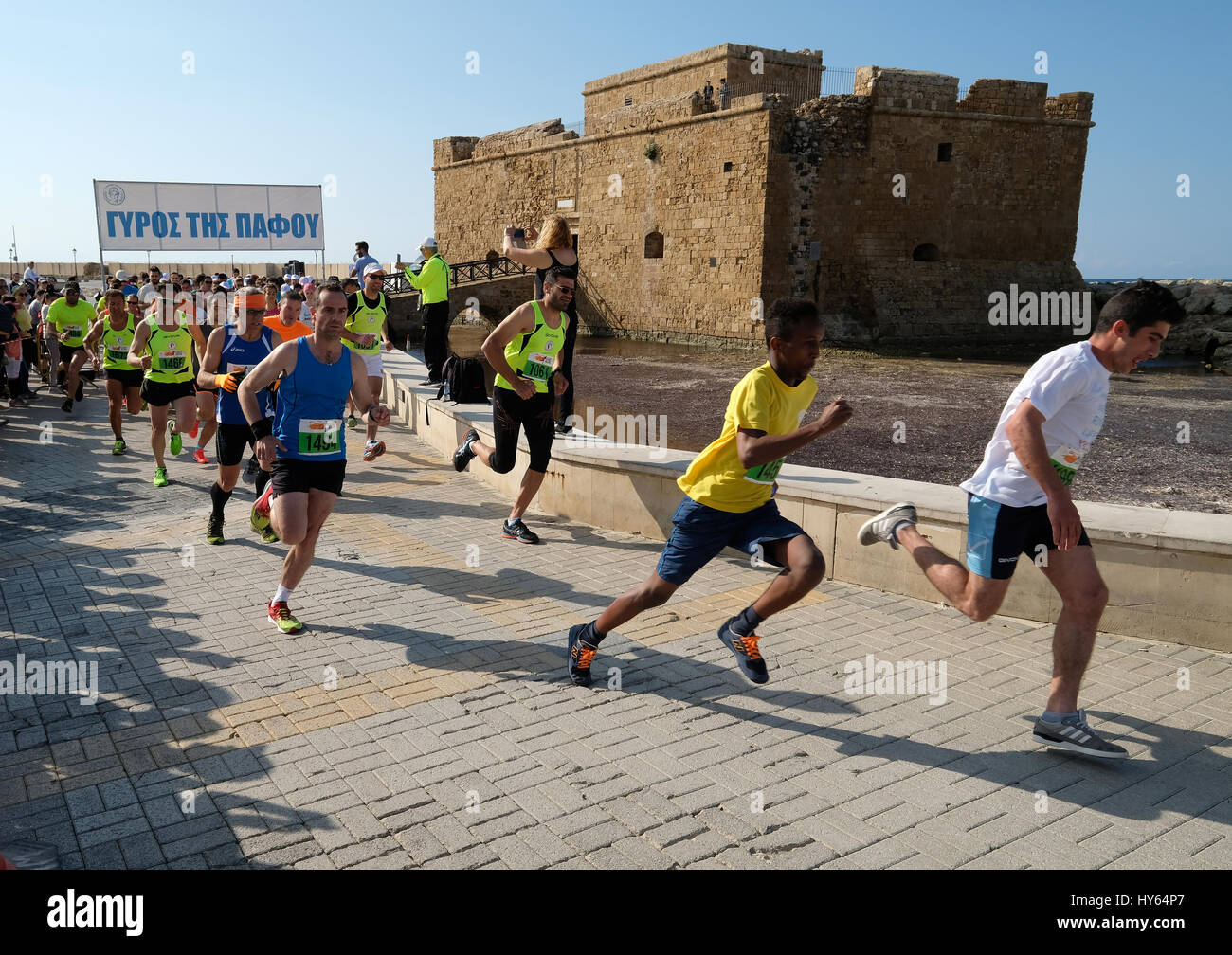 Athletes leave the start of the 4k road race in front of Paphos Castle,  Paphos Harbour, Cyprus. - Stock Image