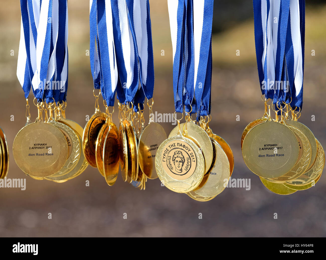 medals shining in the sunshine at the start of the 4k road race in front of Paphos Castle  in Paphos harbour, Cyprus. - Stock Image