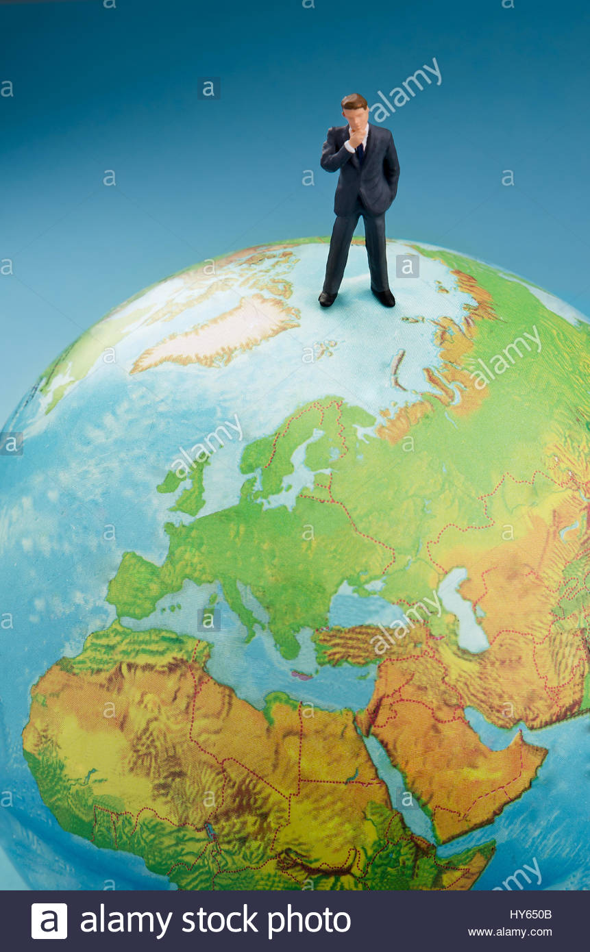 Businessman standing on top of world globe - Stock Image