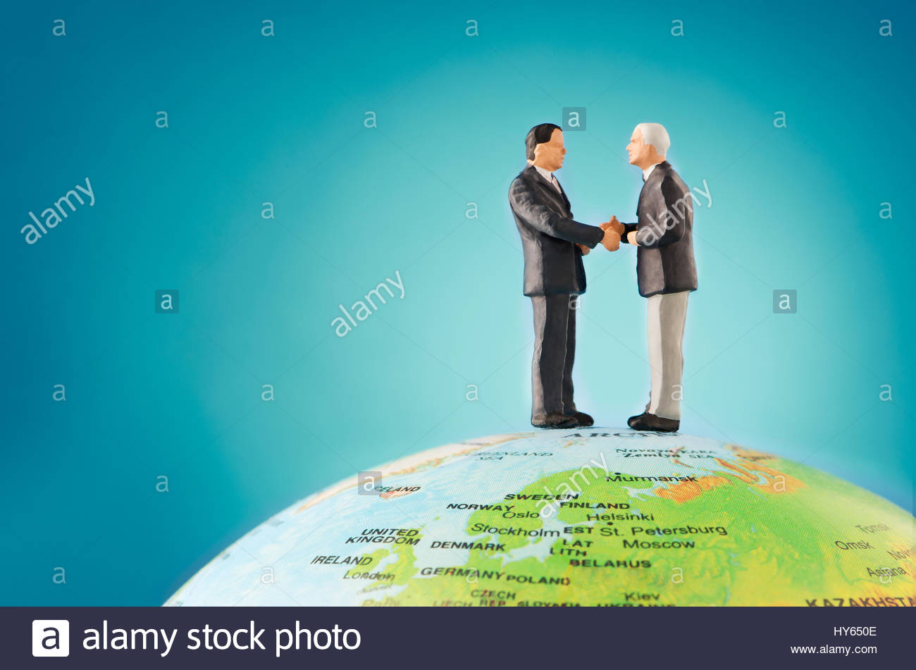 Two businessman shaking hands on top of the world - Stock Image