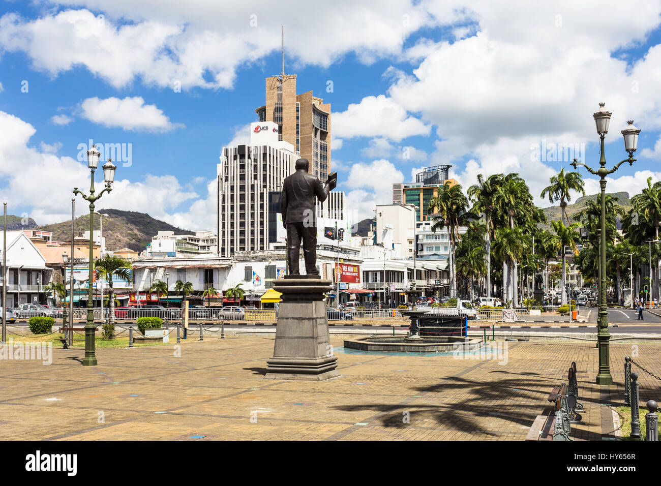 PORT LOUIS, MAURITIUS - NOVEMBER 18, 2016: A statue overlooks the waterfront promenade in front of the he modern Stock Photo