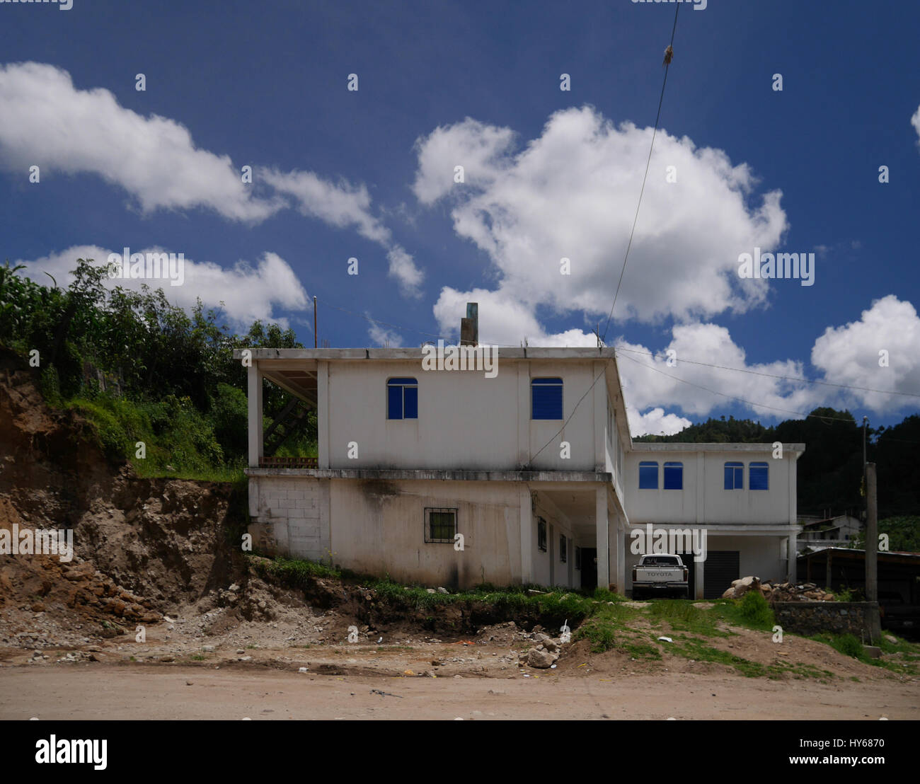 White fluffy clouds above single houses - Stock Image