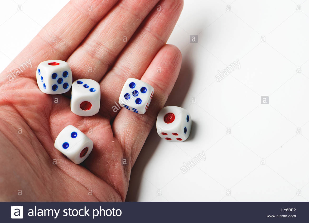 Hand throwing dice on white background. Isolated. Stock Photo