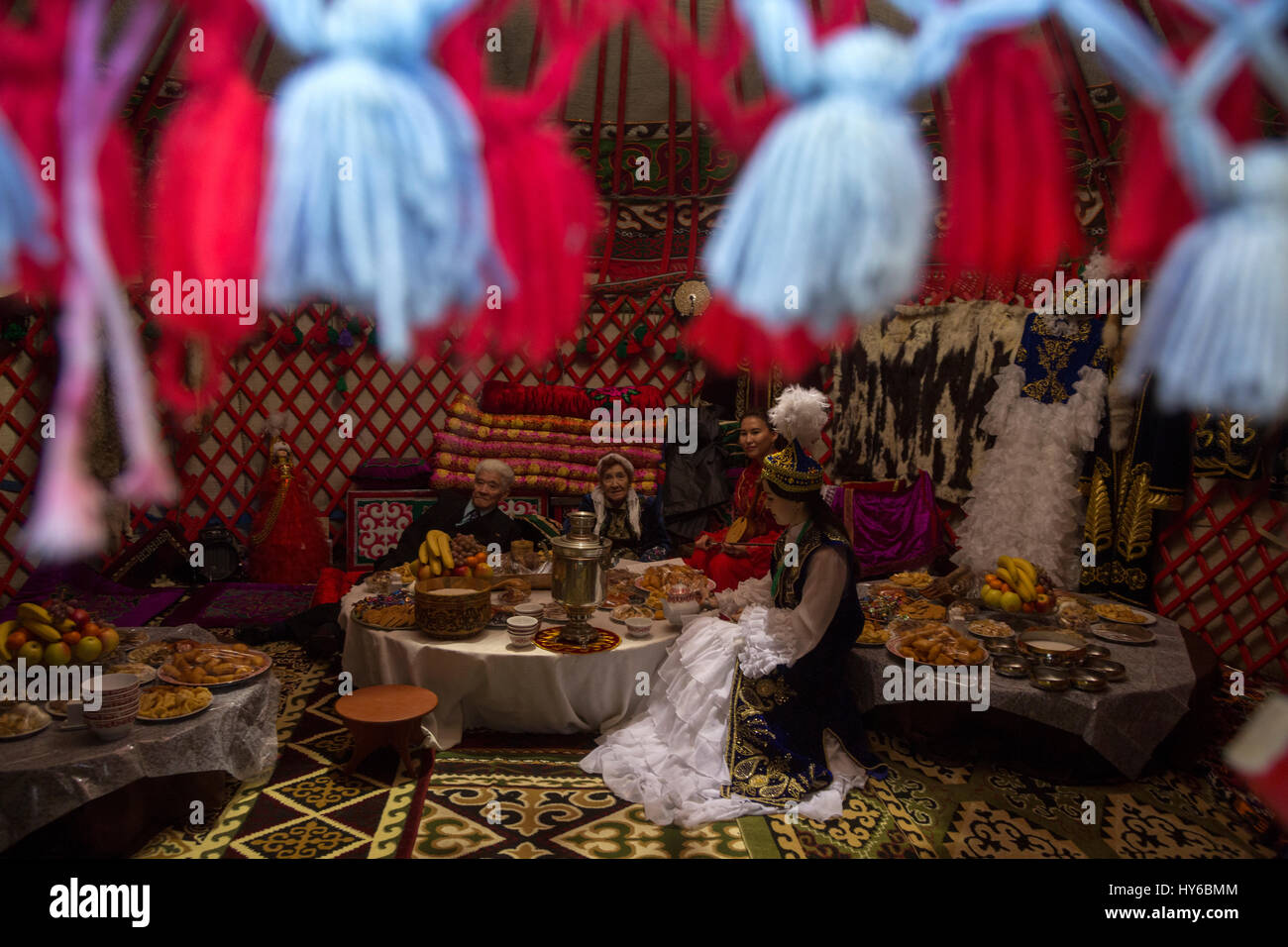 Traditional kazakh family waits for guests in a traditional yurt during the Nowruz holiday - Stock Image