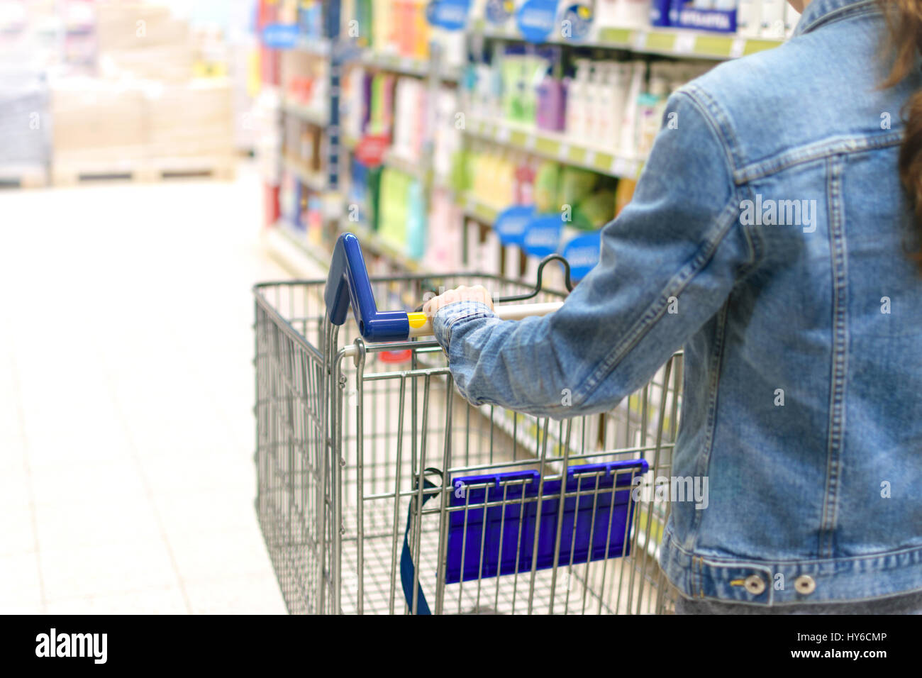 Young woman pushing empty shopping cart in a supermarket - Stock Image