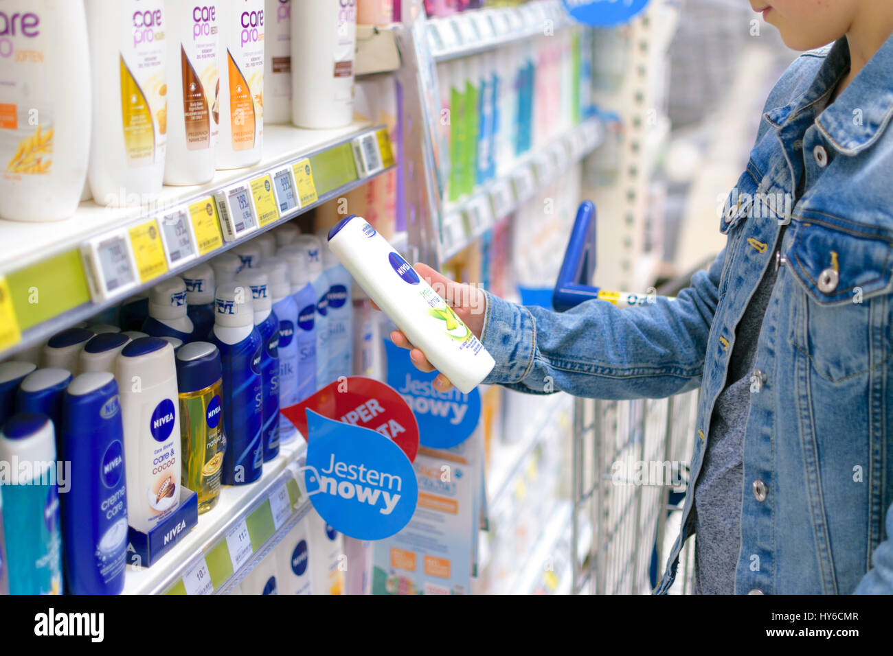 Nowy Sacz, Poland - March 29, 2017:  Young woman in front of aisle with a variety of personal care  products of - Stock Image